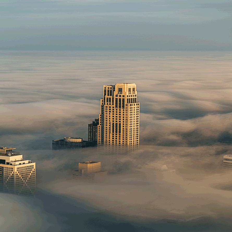 Wolkenkratzer, der aus einer Nebeldecke ragt und damit den Erfolg durch eine Keyword Analyse symbolisiert